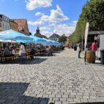 Blick auf das Stadtparkett mit den Biertischen und den Weinständen der teilnehmenden Winzern bei strahlendem Sonnenschein.
